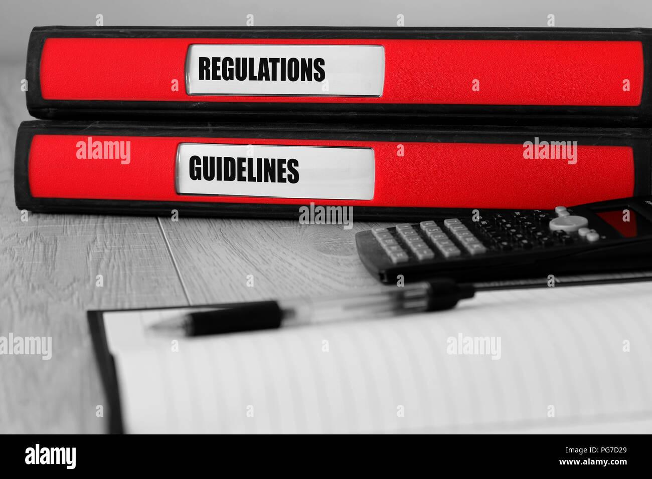 Carpetas rojas con reglamentaciones y directrices escritas en la etiqueta de un escritorio con color selectivo Imagen De Stock