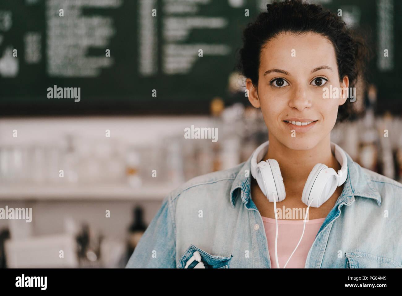 Mujer joven con auriculares, trabajan en espacio de coworking Foto de stock