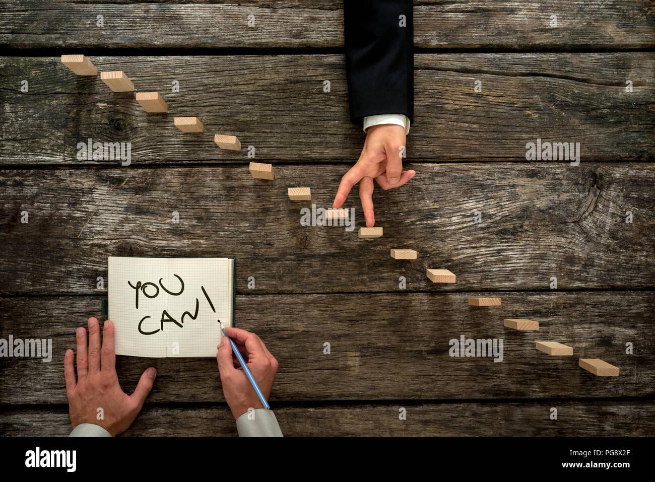 Imagen conceptual del crecimiento personal y el desarrollo profesional con el empresario caminar sus dedos hasta una escalera de madera mientras un colega o mentor encourag Imagen De Stock