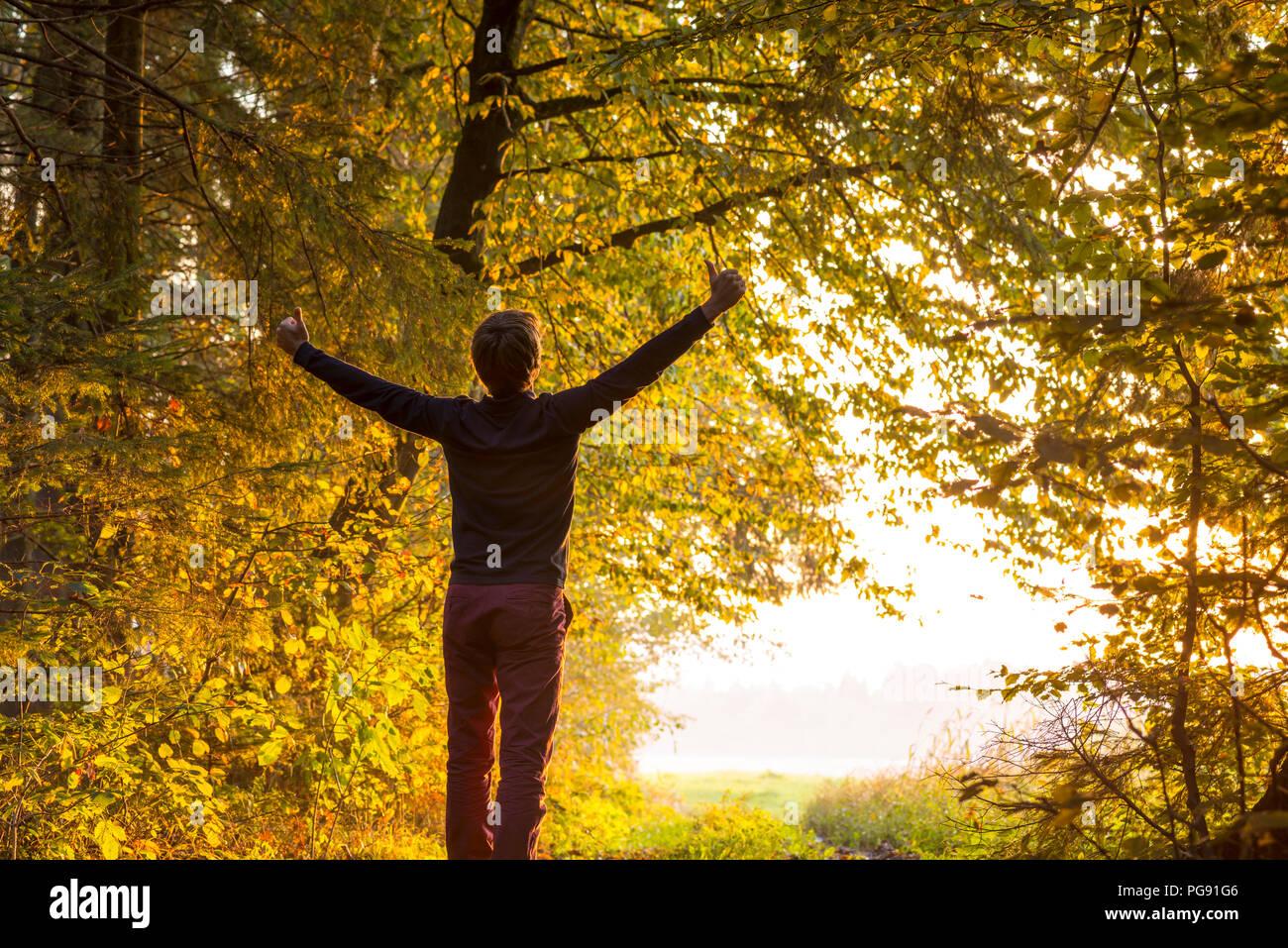 Joven parado en el borde del área boscosa levanta los brazos en celebración orientado hacia una brillante luz solar esperándolo justo fuera de la palestra Imagen De Stock