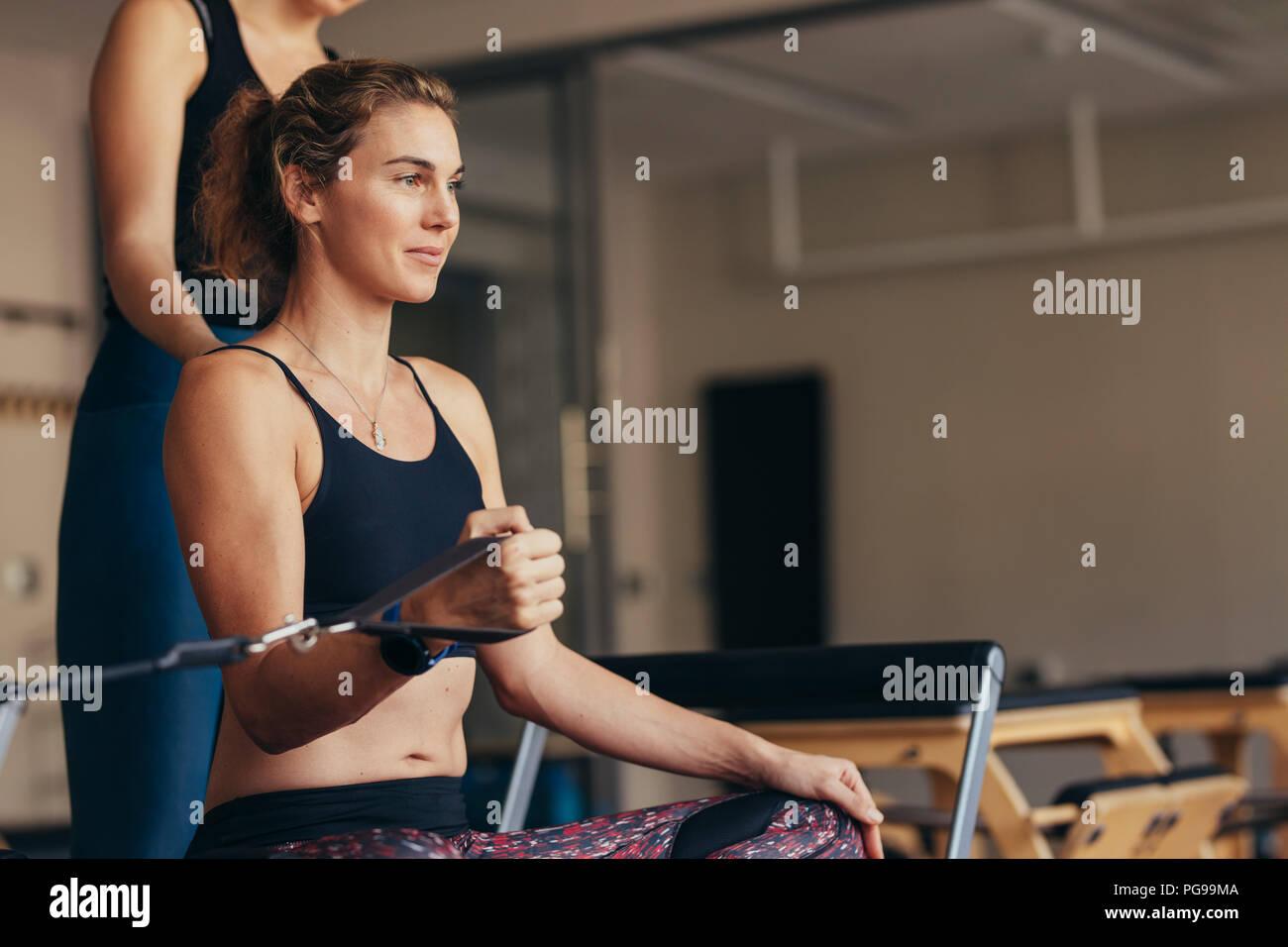 Una mujer sentada sobre una máquina de entrenamiento Pilates tirando de banda elástica con su mano. Imagen De Stock