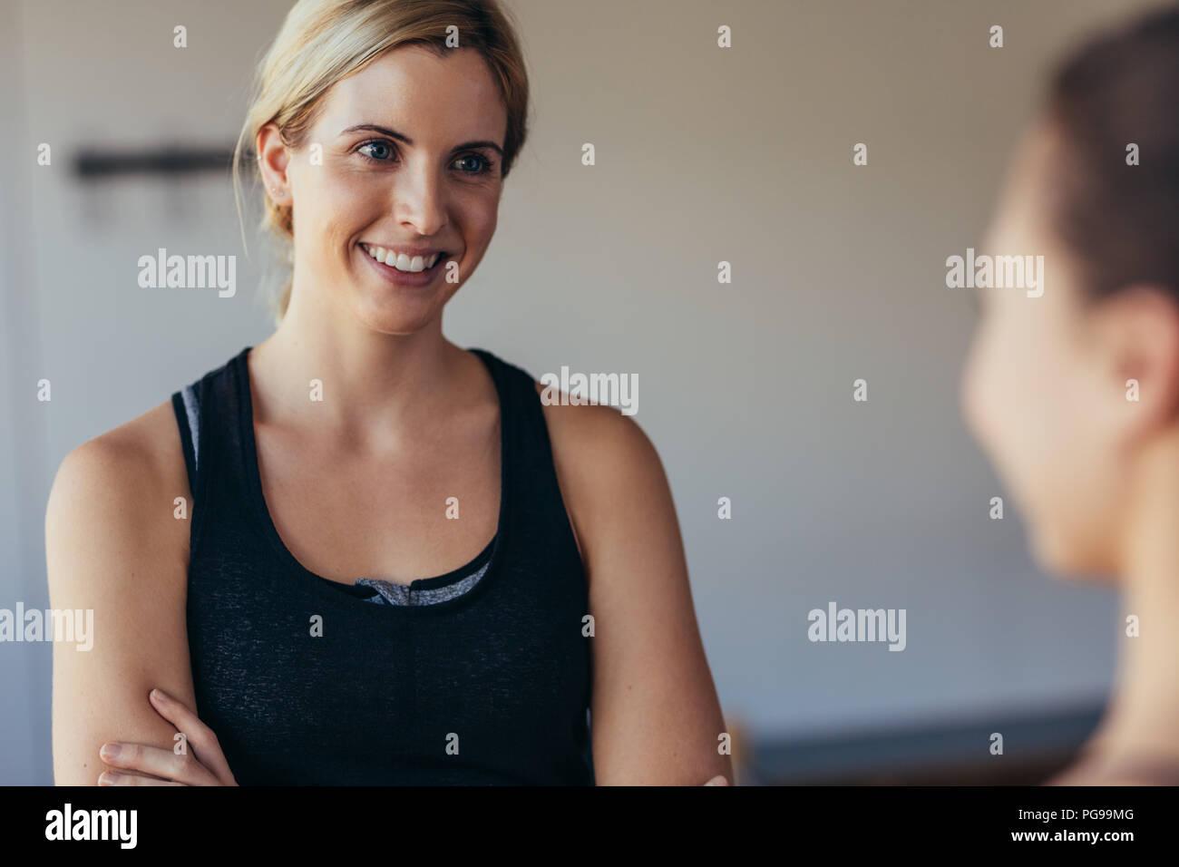 Mujer sonriente en fitness wear en un gimnasio de entrenamiento Pilates. Mujer hablando con un amigo en el gimnasio. Imagen De Stock