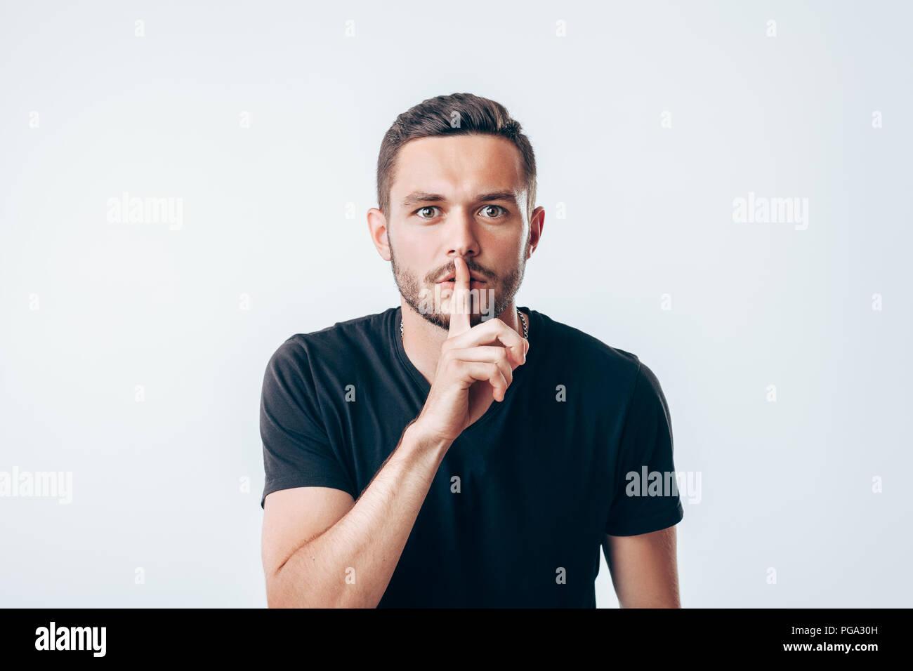 Joven Hombre sujetando el dedo índice sobre los labios pidiendo silencio. Concepto secreto Foto de stock