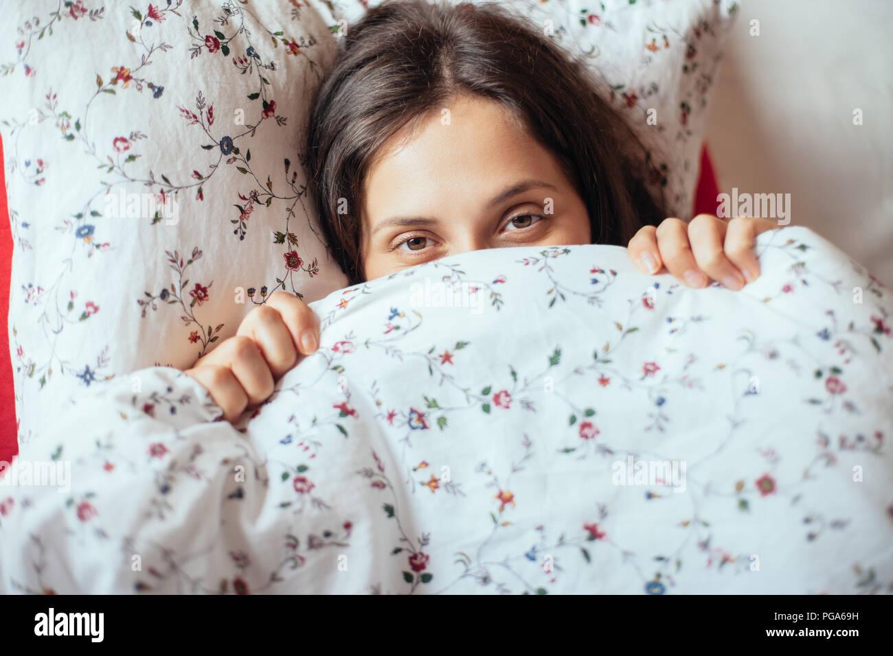 Joven mire debajo de su cama, manta en primer plano. Bella mujer ocultando cara Imagen De Stock