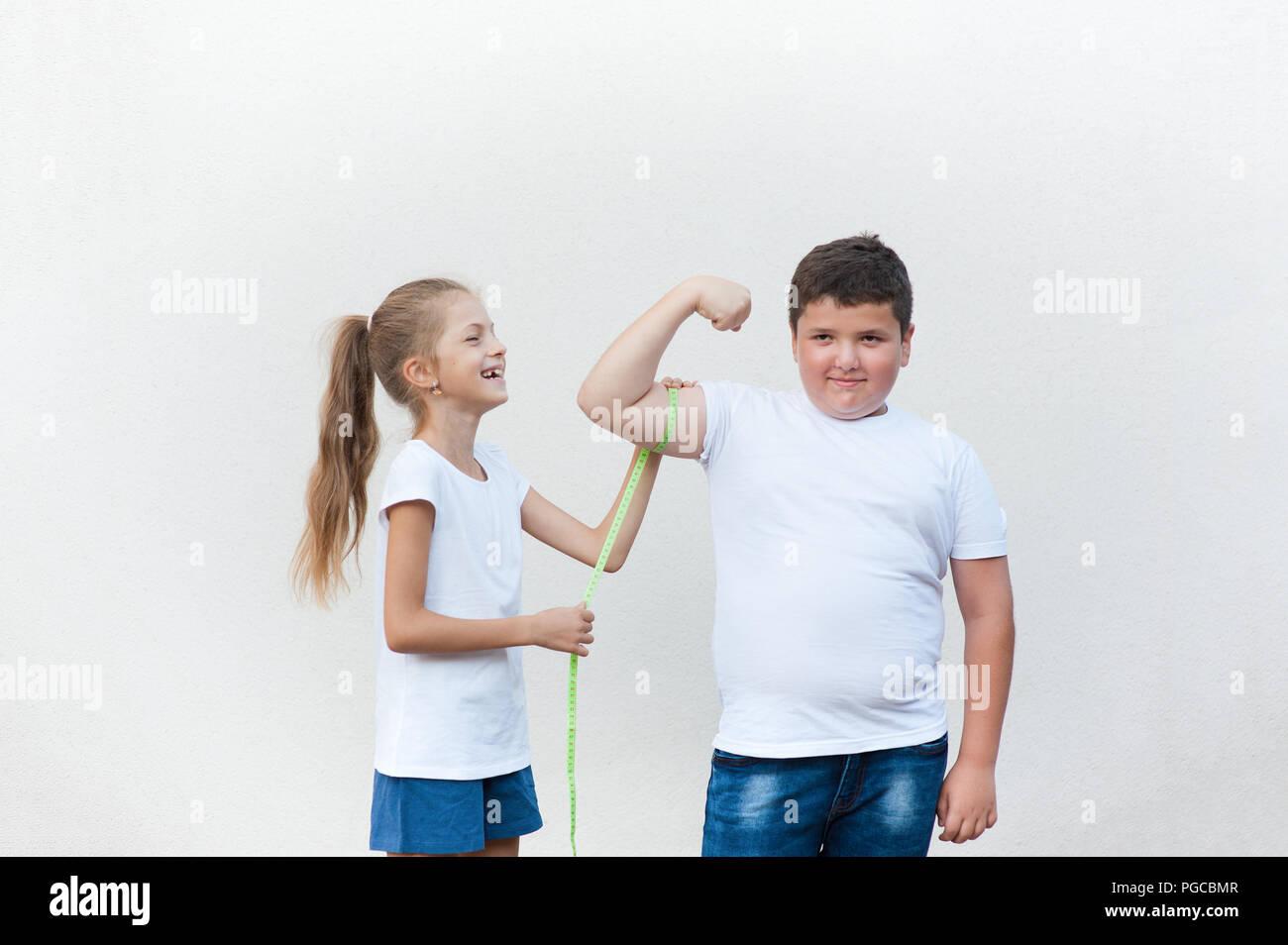 Bastante riendo caucásico niña sana delgado lindo medición Fat Boy músculo bíceps con cinta adhesiva. Imagen De Stock
