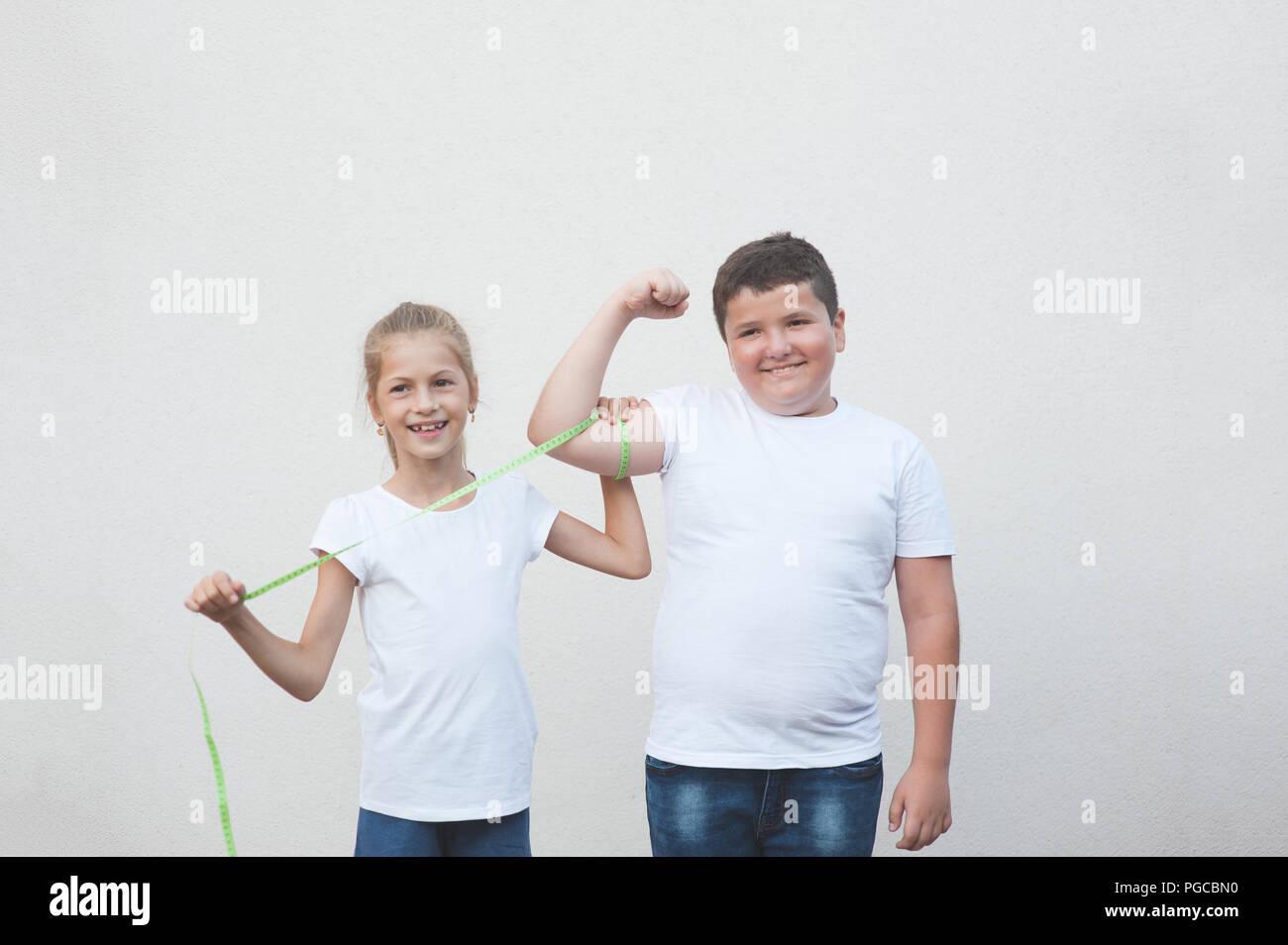 Hermosa niña caucásica slim feliz Medición de espesor cute boy gran músculo con cinta adhesiva. Imagen De Stock