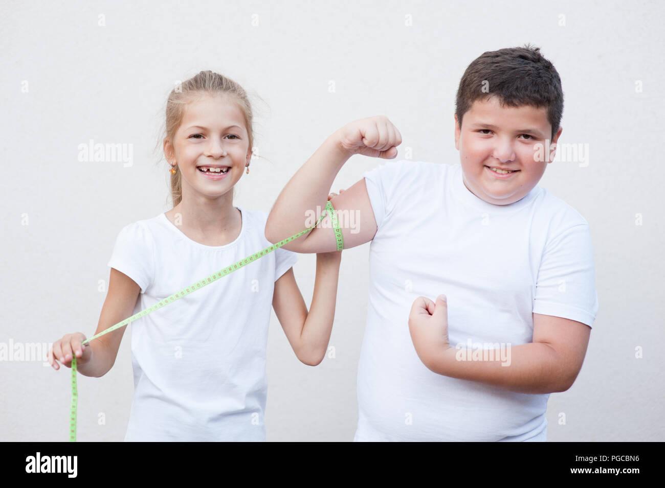 Hermosa flaca feliz pequeña niña sonriente medición big fat boy tamaño muscular por cinta Imagen De Stock