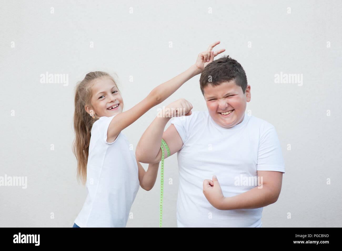 Gracioso delgado caucásica pequeña niña sonriente medición Fat Boy por cinta muscular jugando Imagen De Stock
