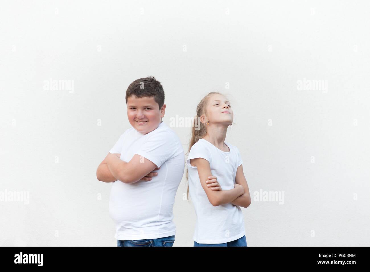 Felices los niños caucásicos guapo en camisetas blancas Fat Boy y Girl delgada espalda sobre fondo brillante Imagen De Stock