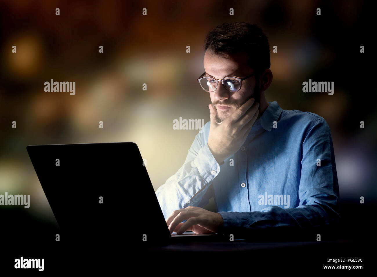 Joven apuesto empresario trabajar hasta tarde en la noche en la oficina Imagen De Stock