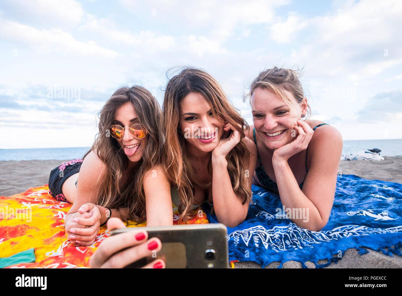 Bonito grupo de hembras jóvenes chica utilizando un teléfono inteligente tumbado en la playa, con el mar y un horizonte evocador en el fondo. alegres personas disfrutando del LIF Imagen De Stock