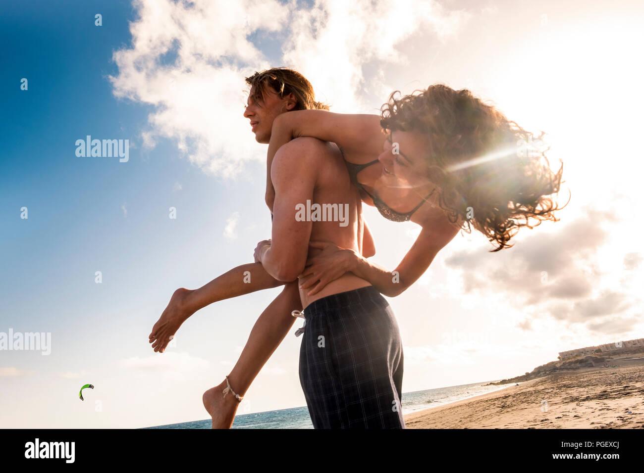 Un montón de diversión en la playa con alegre y hermosa pareja caucásica. El hombre llevar la chica guapa en su hombro como una bolsa y todos se ríen mucho y Imagen De Stock