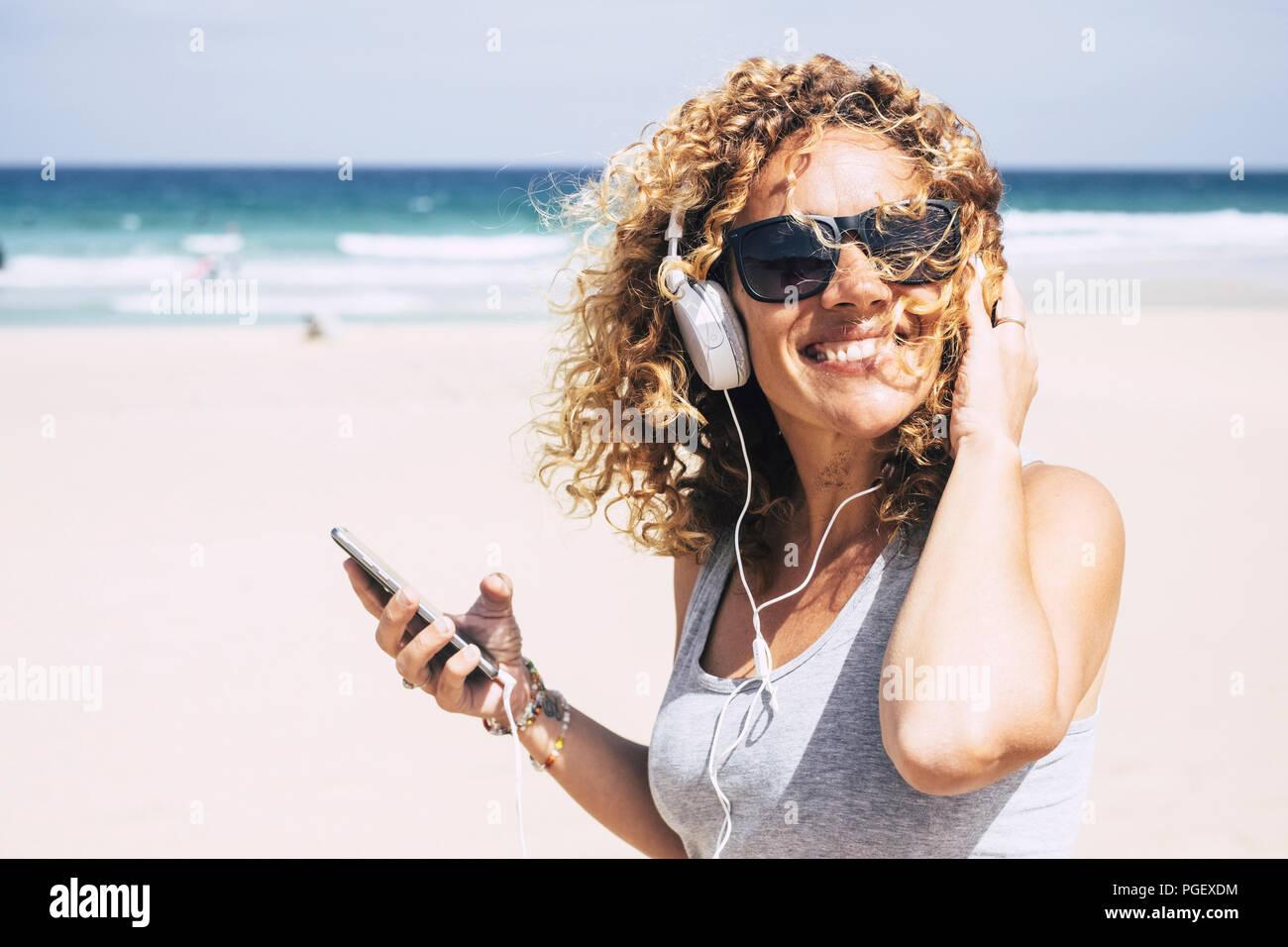 Atractiva alegre hermosa mujer de mediana edad caucásico sonriente en la playa en lugar tropical mientras escucha música con el teléfono inteligente. Personas enjoyi Imagen De Stock