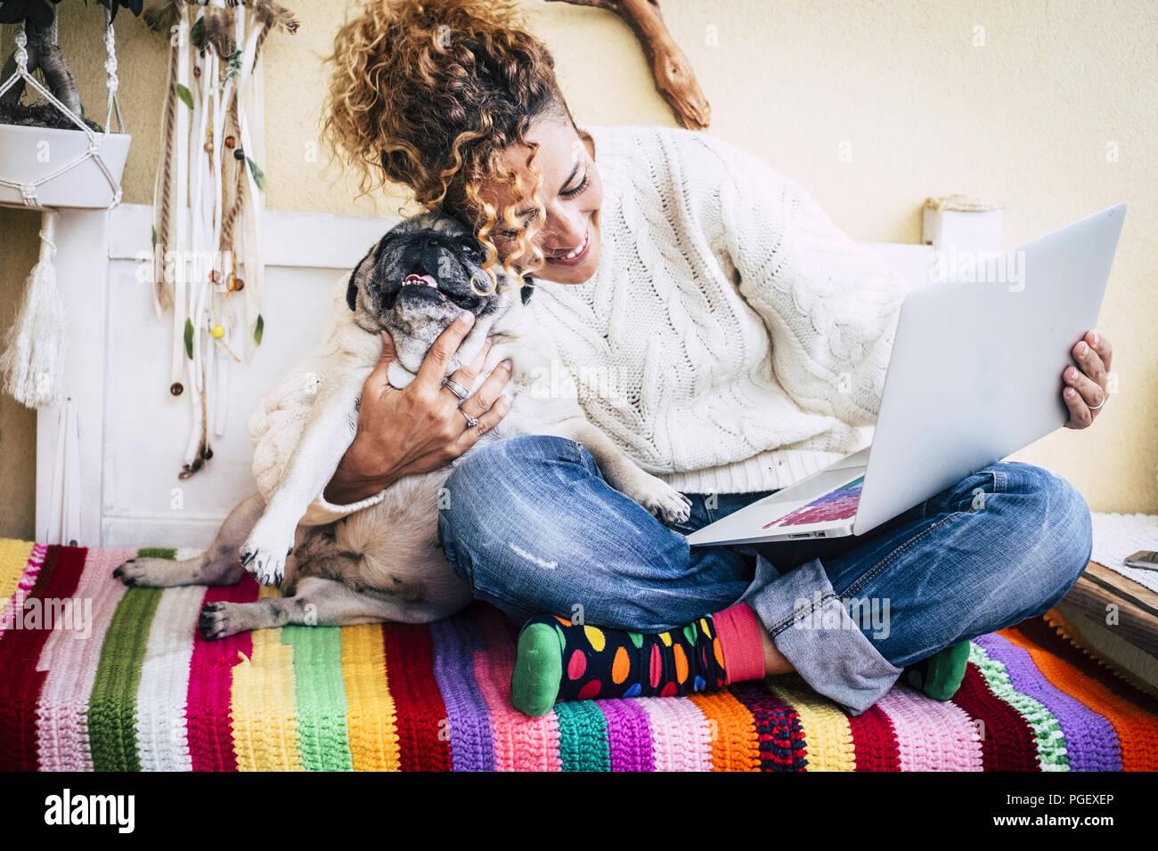 Mejores amigos real alegre mujer trabajando en el portátil en la terraza en casa mientras abrazo a su mejor Amor y amigos sonrientes pug perro sentado a su izquierda. co Foto de stock