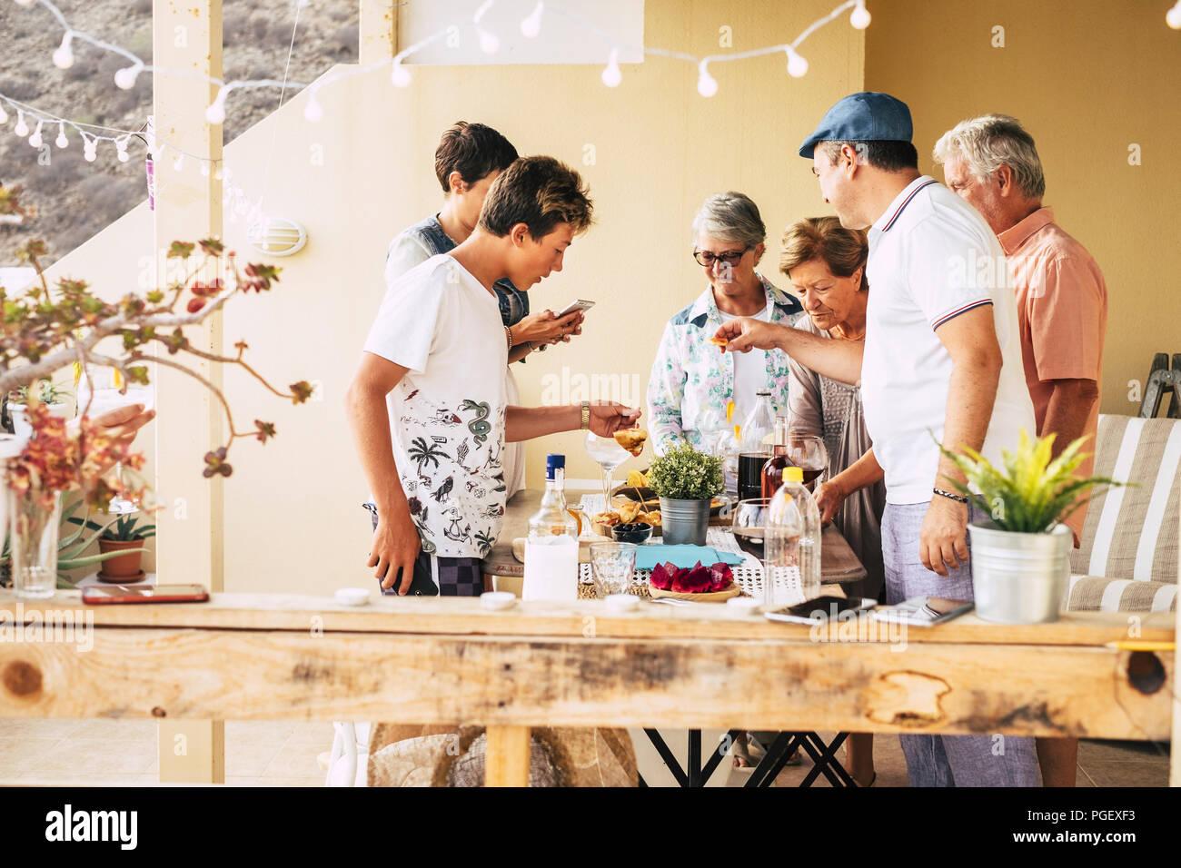 Grupo de personas de diferentes edades desde adolescente madura divirtiéndonos juntos comer y beber en la amistad en el hogar al aire libre en la terraza. mix Imagen De Stock