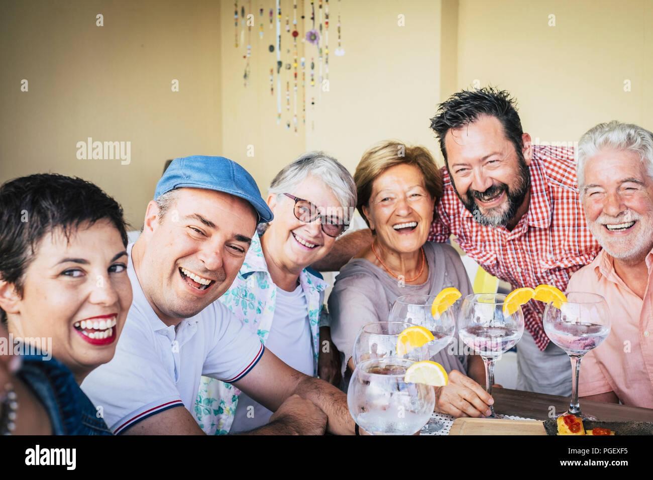 Grupo de edades mixtas del Pueblo Caucasiano divirtiéndonos juntos celebrando un evento bebiendo vino tinto con cócteles de vodka blanco. vacaciones concepto con HAP. Imagen De Stock