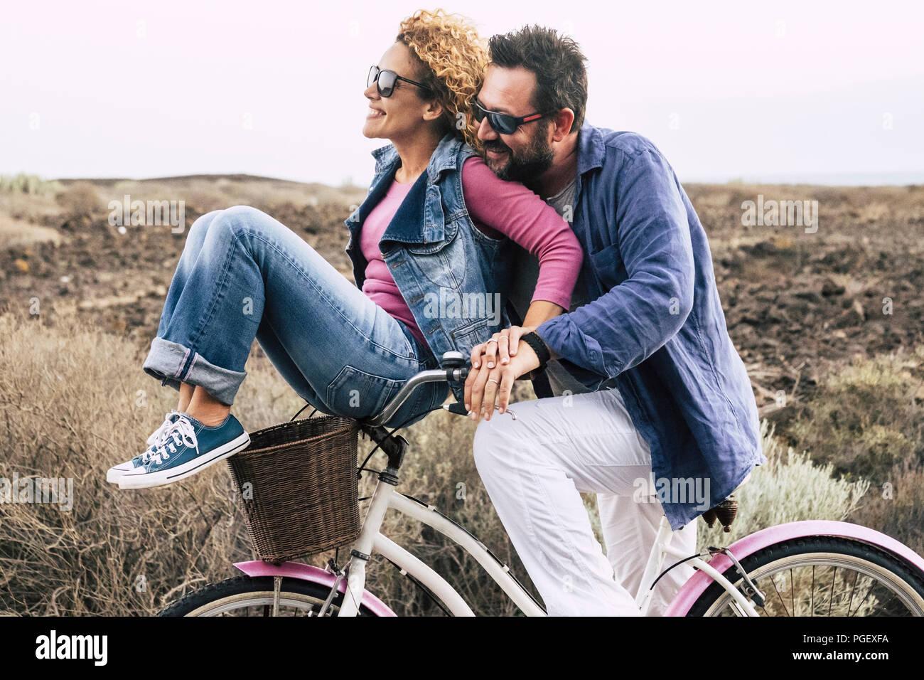 Feliz pareja caucásica, adultos divirtiéndose con bicicleta en actividad de ocio al aire libre. Concepto de activo juguetón personas con bicicleta durante vacaciones - everyd Imagen De Stock