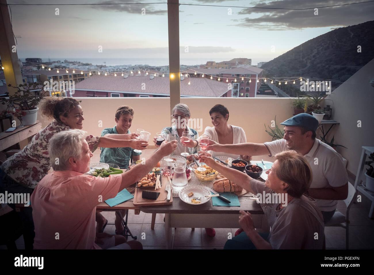 Grupo de personas de diferentes edades en la amistad comen juntos una cena con vino vítores y disfrutar del estilo de vida. La felicidad y alegría para amigos Foto de stock