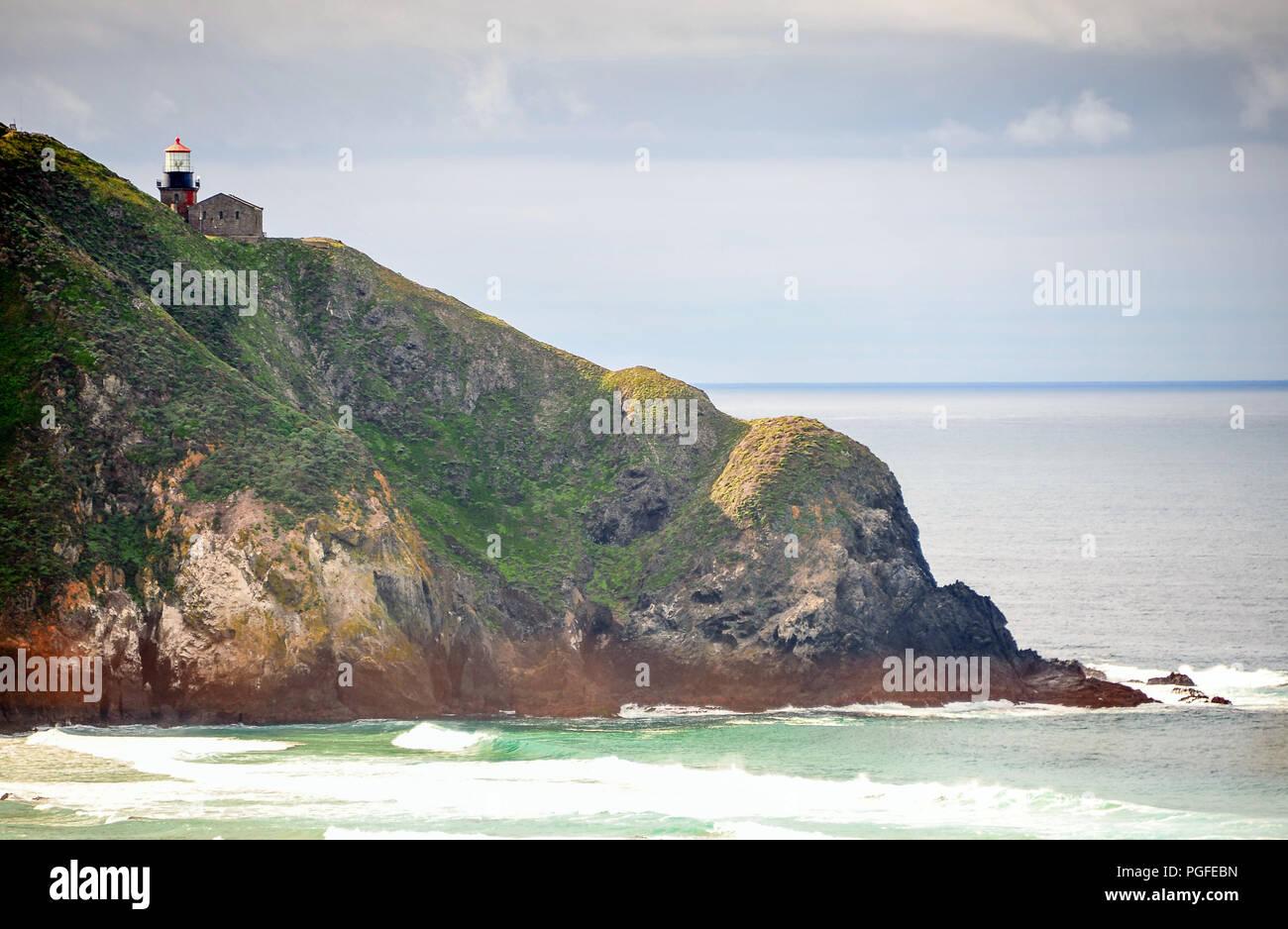Monterey, California: escena colorida, Lighthouse Point Sur en la cima de una roca volcánica dramático con mar brumoso/fondo del cielo Imagen De Stock
