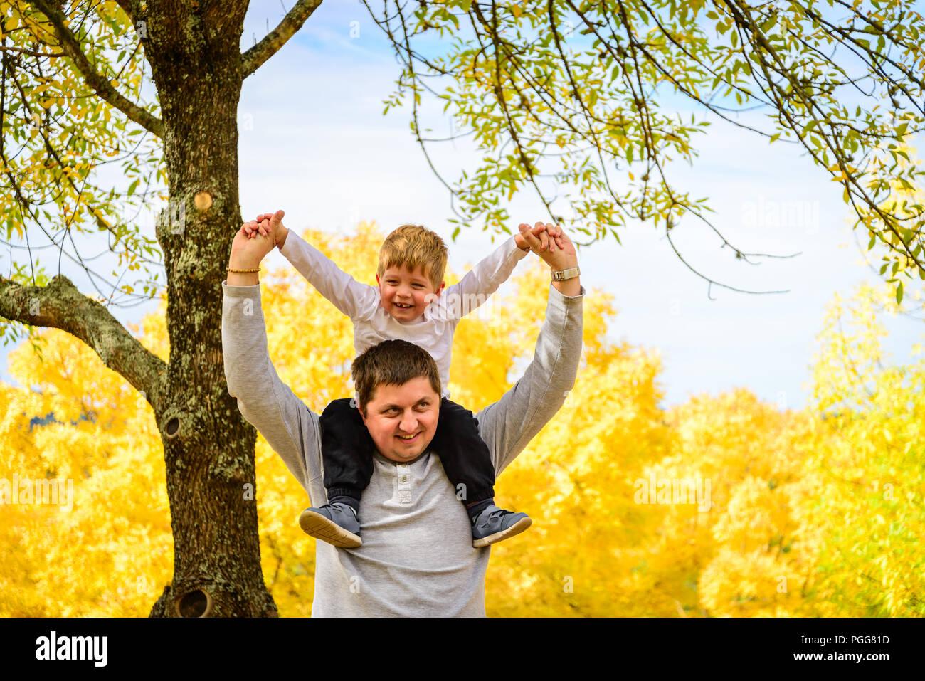 Padre dando su hijo piggyback paseo en otoño, el parque de las colinas de Adelaida, Australia del Sur Imagen De Stock