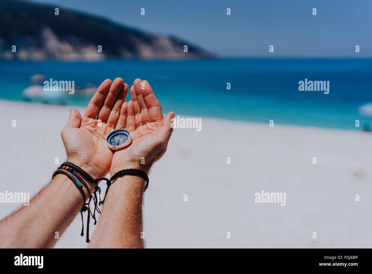 Las palmas de las manos abiertas sosteniendo la brújula de metal contra la arena y el mar azul. Buscando su camino concepto. Punto de vista POV Imagen De Stock
