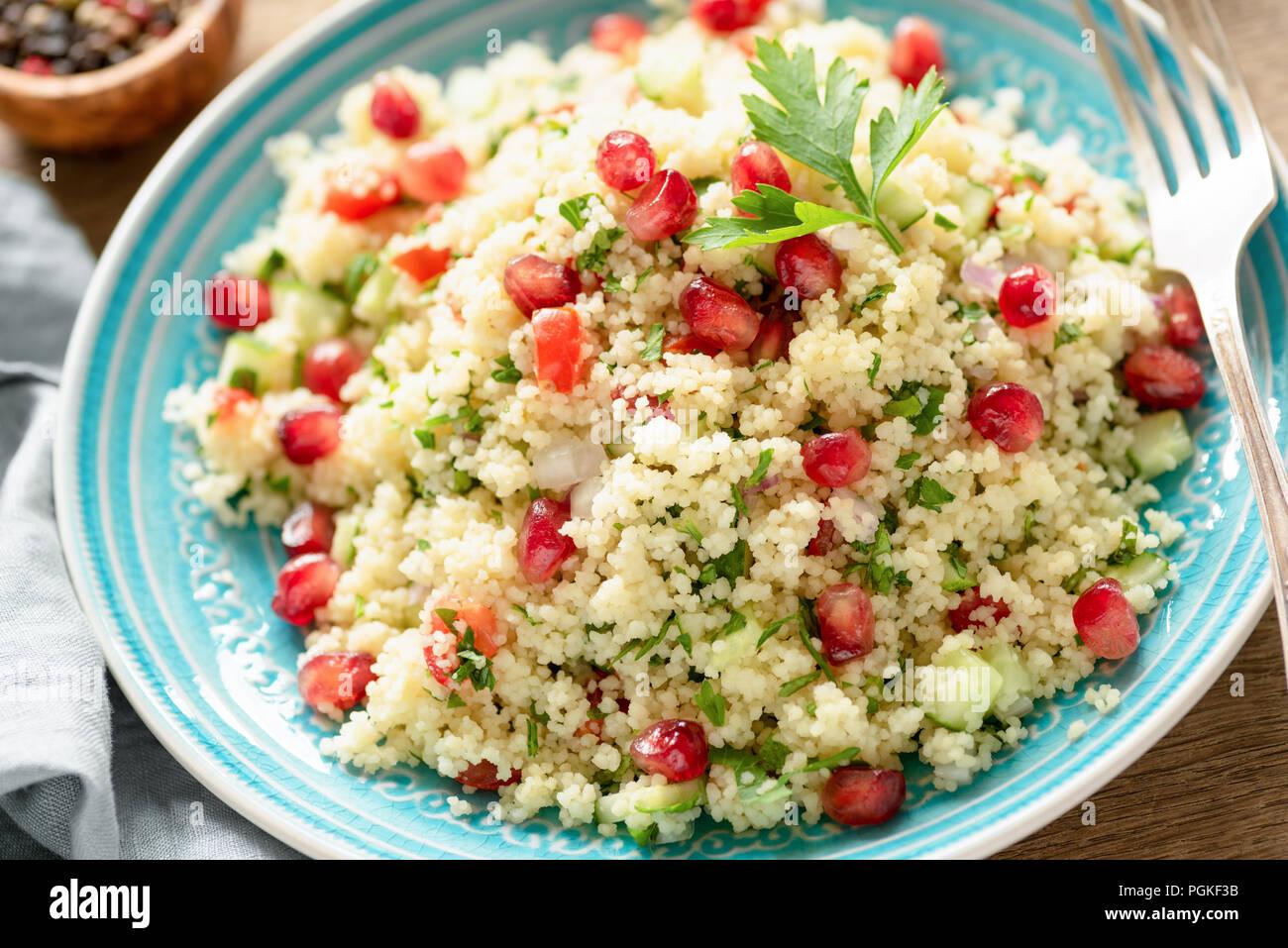 Tabbouleh ensalada con semillas de granada sobre placa de turquesa. Visión más cercana. Vegetariana saludable ensalada árabe Imagen De Stock