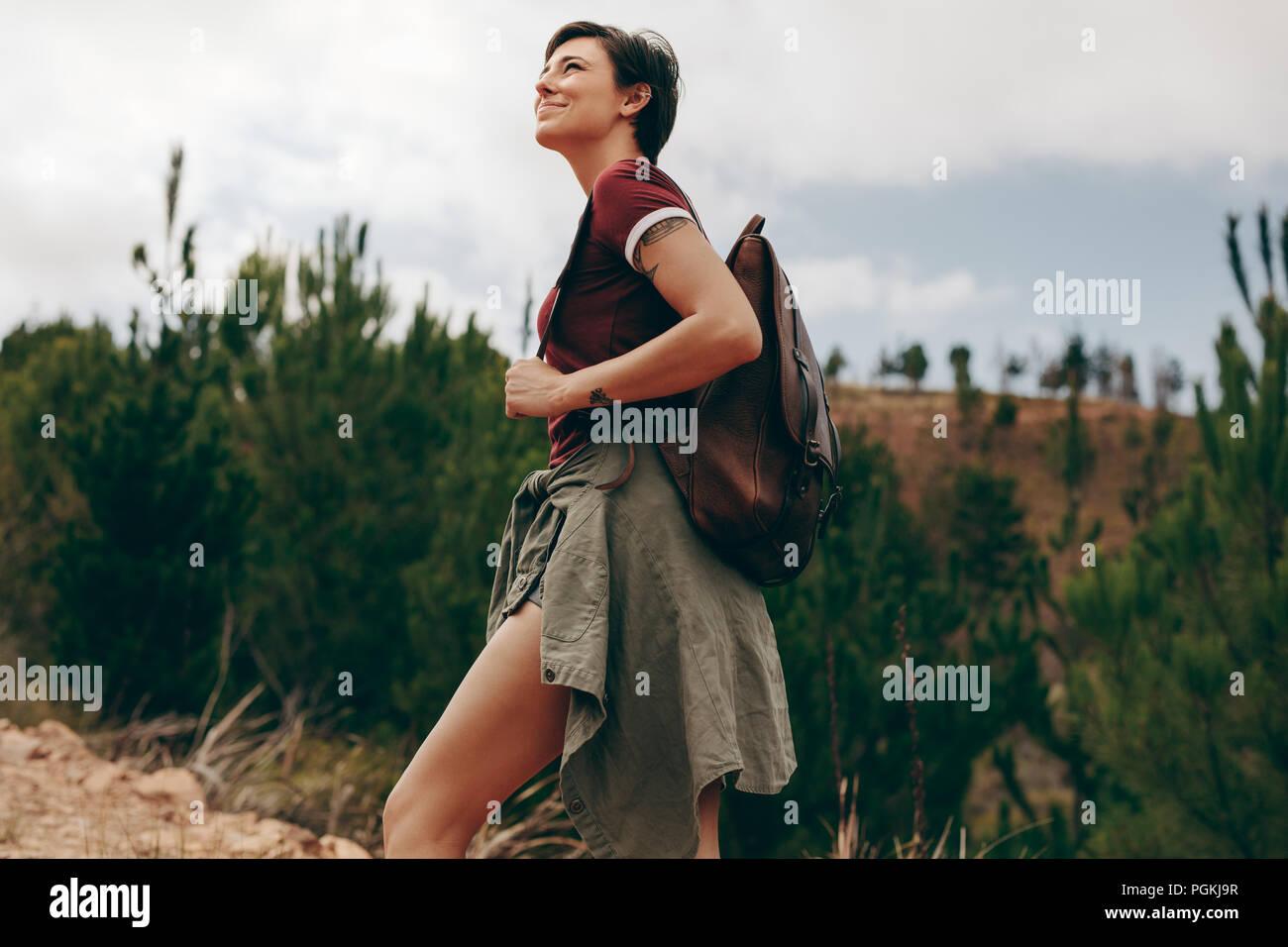 Mujer alegre y caminatas en el bosque. La mujer llevaba una bolsa caminando a través del bosque con árboles en el fondo Imagen De Stock