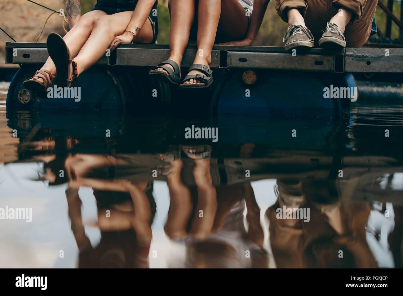 Amigos de vacaciones sentados juntos en un dique flotante de plástico de barriles. Amigos sentado cerca del lago con su reflejo en el agua. Imagen De Stock