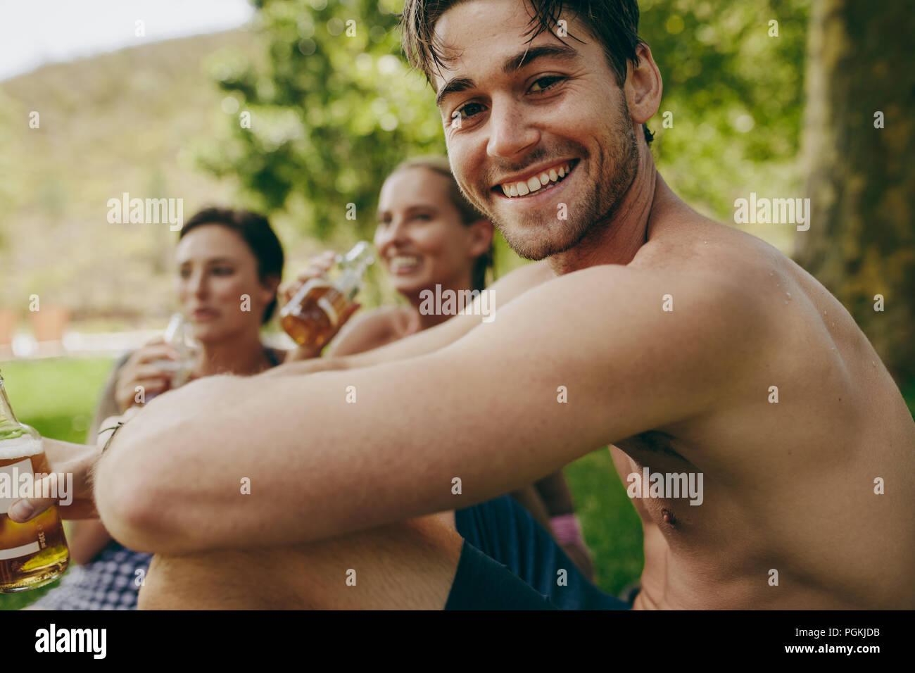 Amigos, disfrutando de las vacaciones en un parque con bebidas. Hombre con dos amigas sentados afuera, bebiendo cerveza. Imagen De Stock