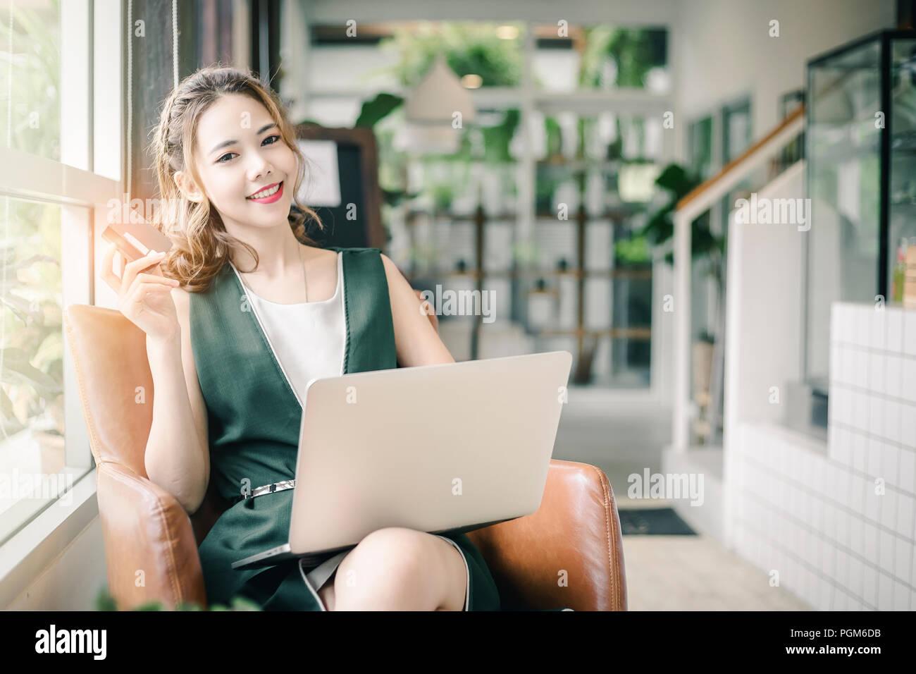 Hermosa mujer asiática la celebración de tarjeta de crédito y trabajando con un portátil o un ordenador portátil. Imagen De Stock