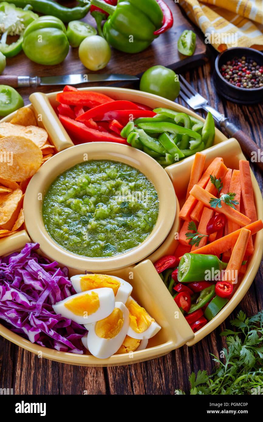 Green salsa verde mexicana y conjunto de verduras frescas picadas, huevos duros y patatas fritas en recipientes en la antigua junta de madera rústica con ingredientes, vertic Imagen De Stock