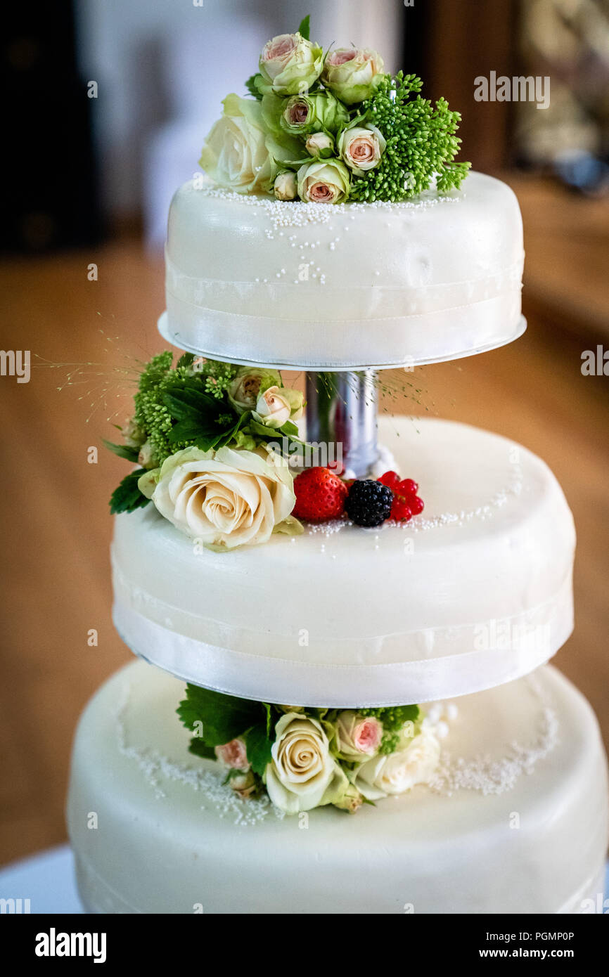 Pastel de boda decorado con frutos y flores. Foto de stock