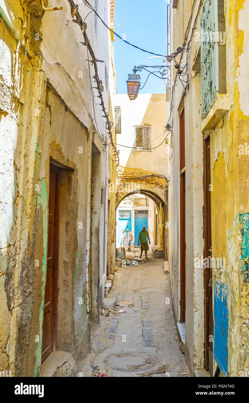 SFAX, Túnez - Septiembre 3, 2015: Caminando por las estrechas calles de la vieja Medina, alineado con el desvencijado edificio sof talleres locales y viviendas, en sept. Imagen De Stock