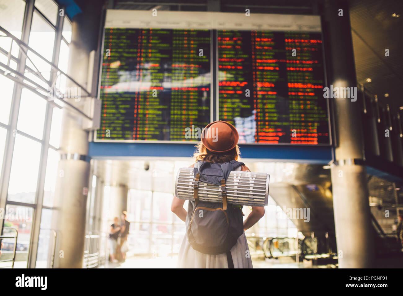 Tema viajar en transporte público. mujer joven de pie con la espalda en el vestido y el sombrero detrás de mochila y equipo de camping para dormir, esterilla aislante buscar Foto de stock