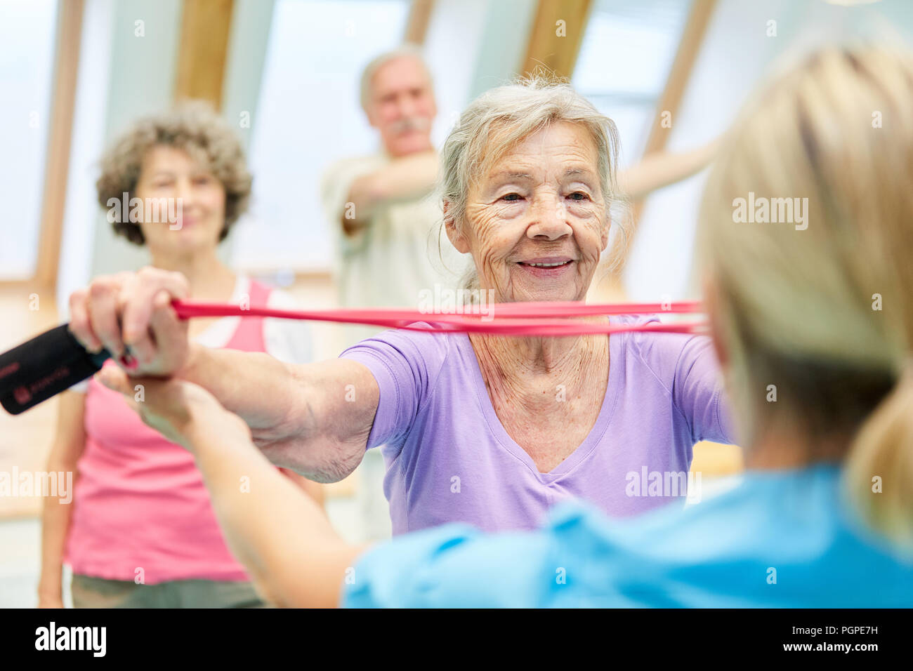 Mujer de clase superior en fisioterapia con entrenador haciendo ejercicio con la banda elástica Imagen De Stock