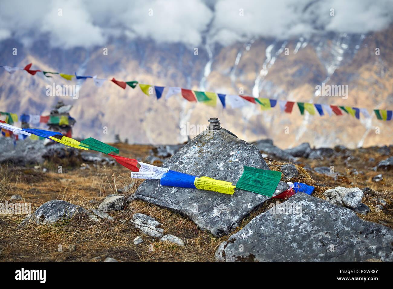Pequeños montones de piedras y banderas de oración tibetano Lung Ta en el Mardi Himal Campamento Base a nublado picos de las montañas del Himalaya en Nepal Foto de stock