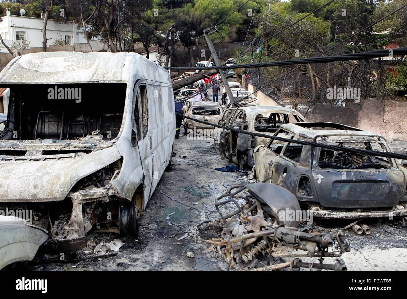 La gente se levanta en medio de los restos calcinados de coches quemados en Mati al este de Atenas, Twin incendios azotan a través de populares zonas costera griega cerca de la ca Foto de stock