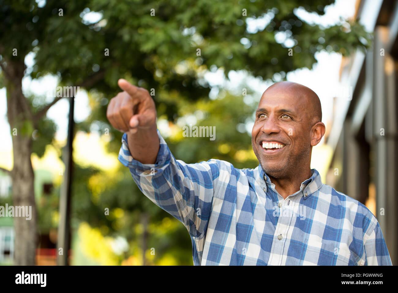 Hombre afroamericano sonriente y apuntando lejos de la cámara. Imagen De Stock