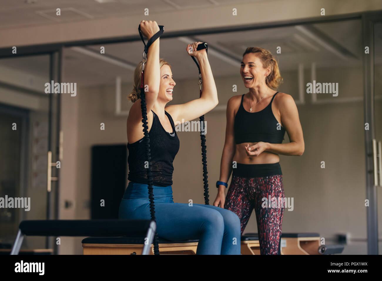 Mujer sonriente tirando de las bandas de estiramiento durante su entrenamiento Pilates. Mujeres en un gimnasio de entrenamiento Pilates riendo mientras se hace ejercicio. Imagen De Stock