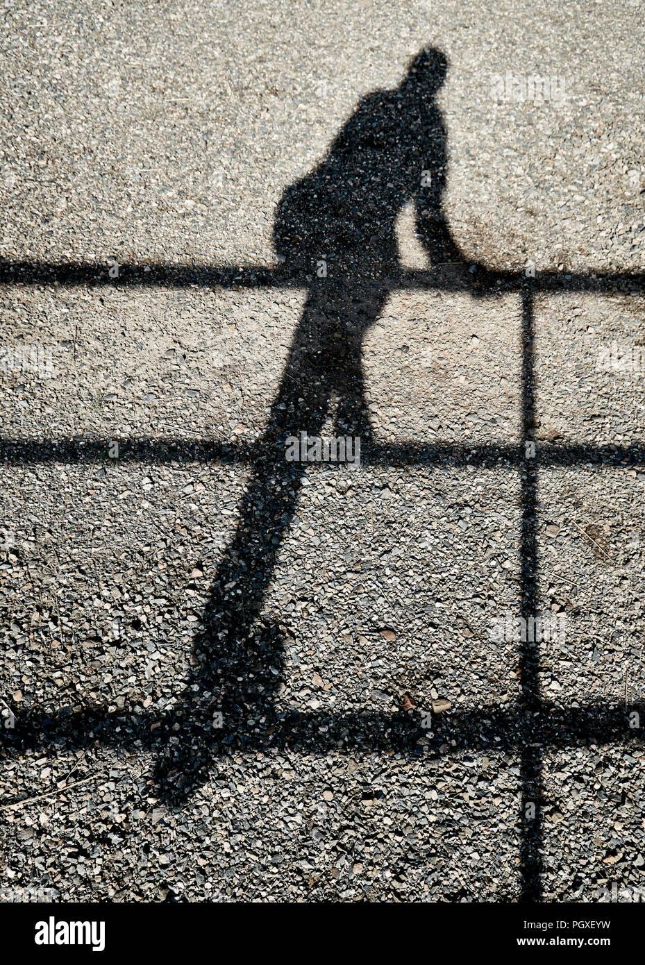Sombra de una persona subiendo una valla Foto de stock