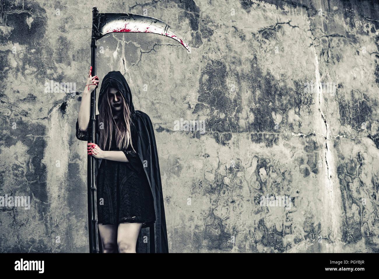 Demon witch con reaper grunge de pie delante de la pared de fondo. Halloween y el concepto religioso. Angel y Demonio Satanás tema. Imagen De Stock