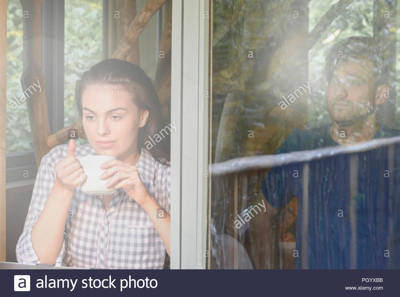 Pareja joven al abrir la ventana de log cabin. Imagen De Stock
