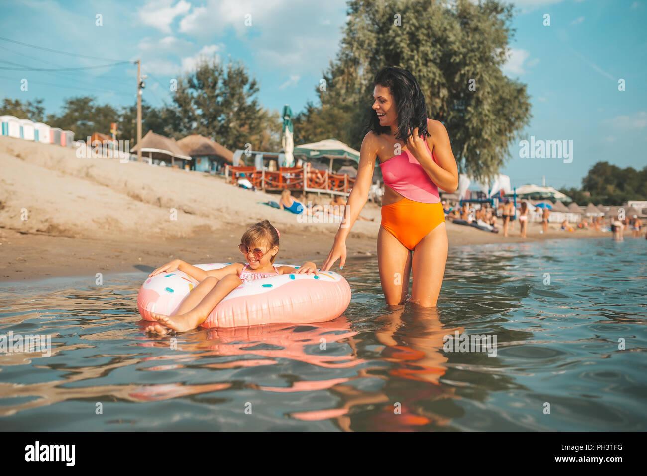 Madre e hija nadar y relajarse en el agua en un donut inflable. Vacaciones de verano Imagen De Stock