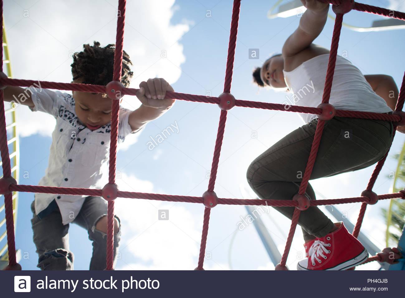 Hermanos jugando en columpios en park Imagen De Stock