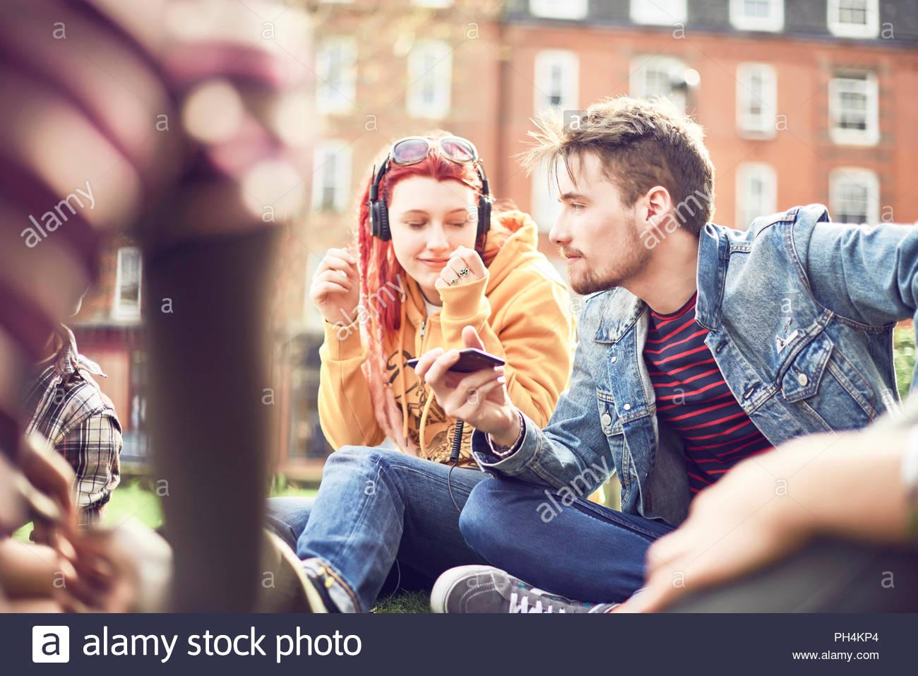 La pareja de adolescentes compartir música en el parque Imagen De Stock