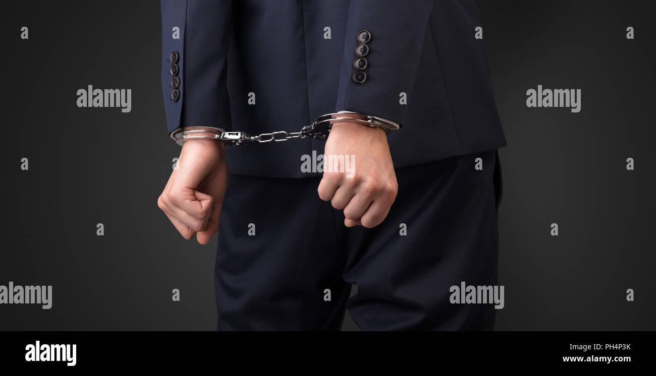 Cerrar ahora hombres arrestados mano con fondo oscuro y esposas Foto de stock
