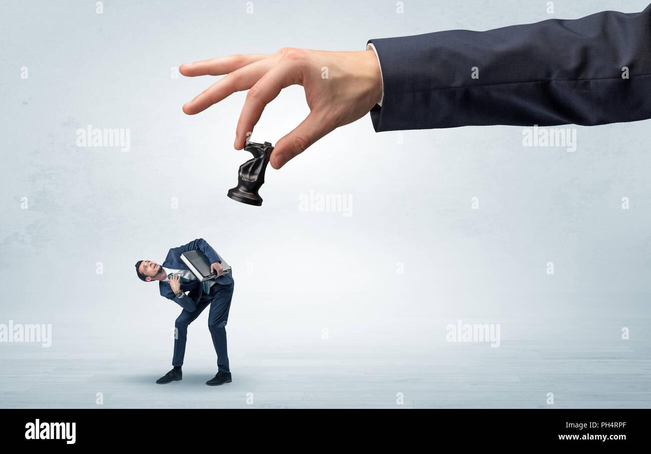 Gran mano sujetando figura de ajedrez y hacia abajo un poco asustado empresario concepto en un espacio de luz Imagen De Stock