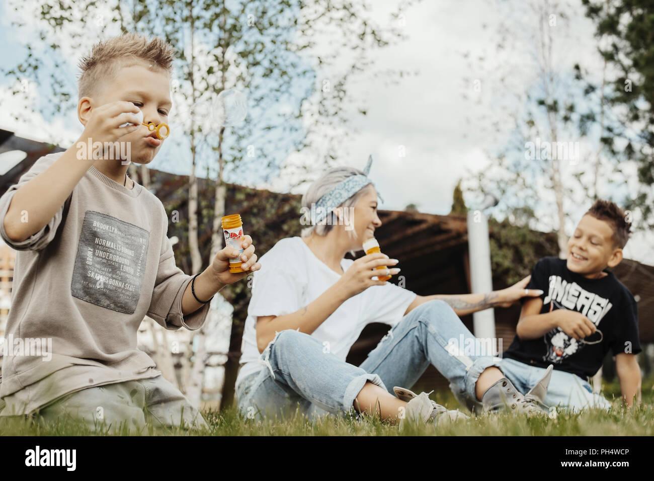 Cerca de la familia soplando burbujas al aire libre en el parque. Imagen De Stock