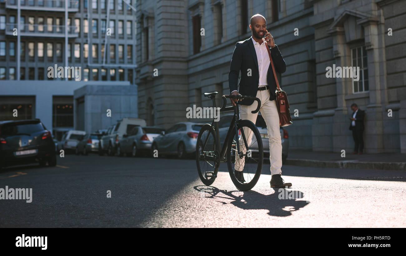 Joven Empresario de caminar al aire libre con una bicicleta y utilizando un teléfono móvil. Hombre africano para ir a trabajar en bicicleta hablando por teléfono celular en las calles de la ciudad. Foto de stock