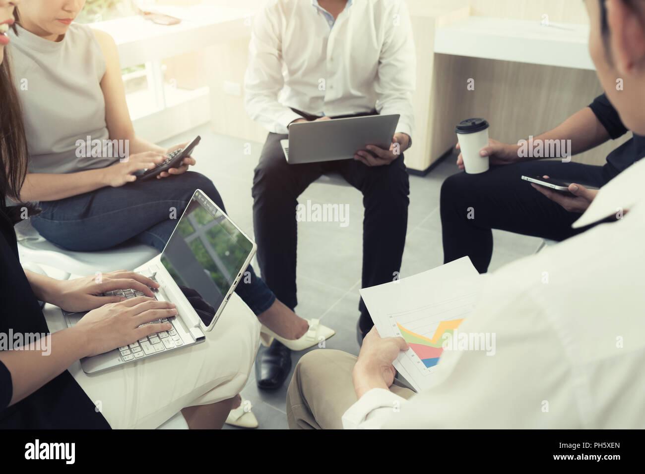 La gente busniess casual reunión en la oficina moderna. Equipo empresarial compañeros compartir documento de informe de negocios. Imagen De Stock